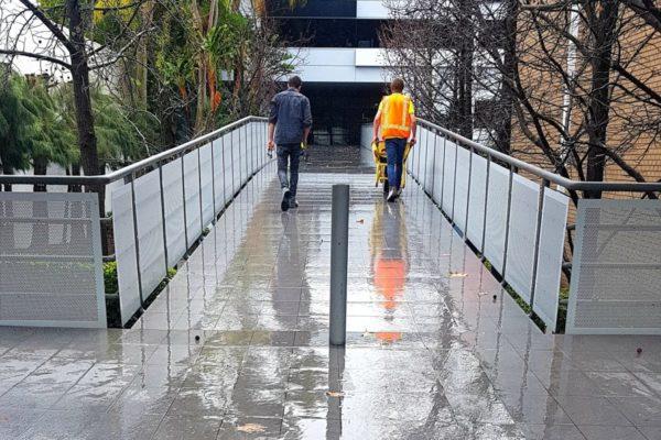 workmen pushing wheelbarrow down a pedestrian bridge