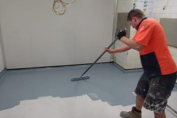 applying floor coating in freezer room