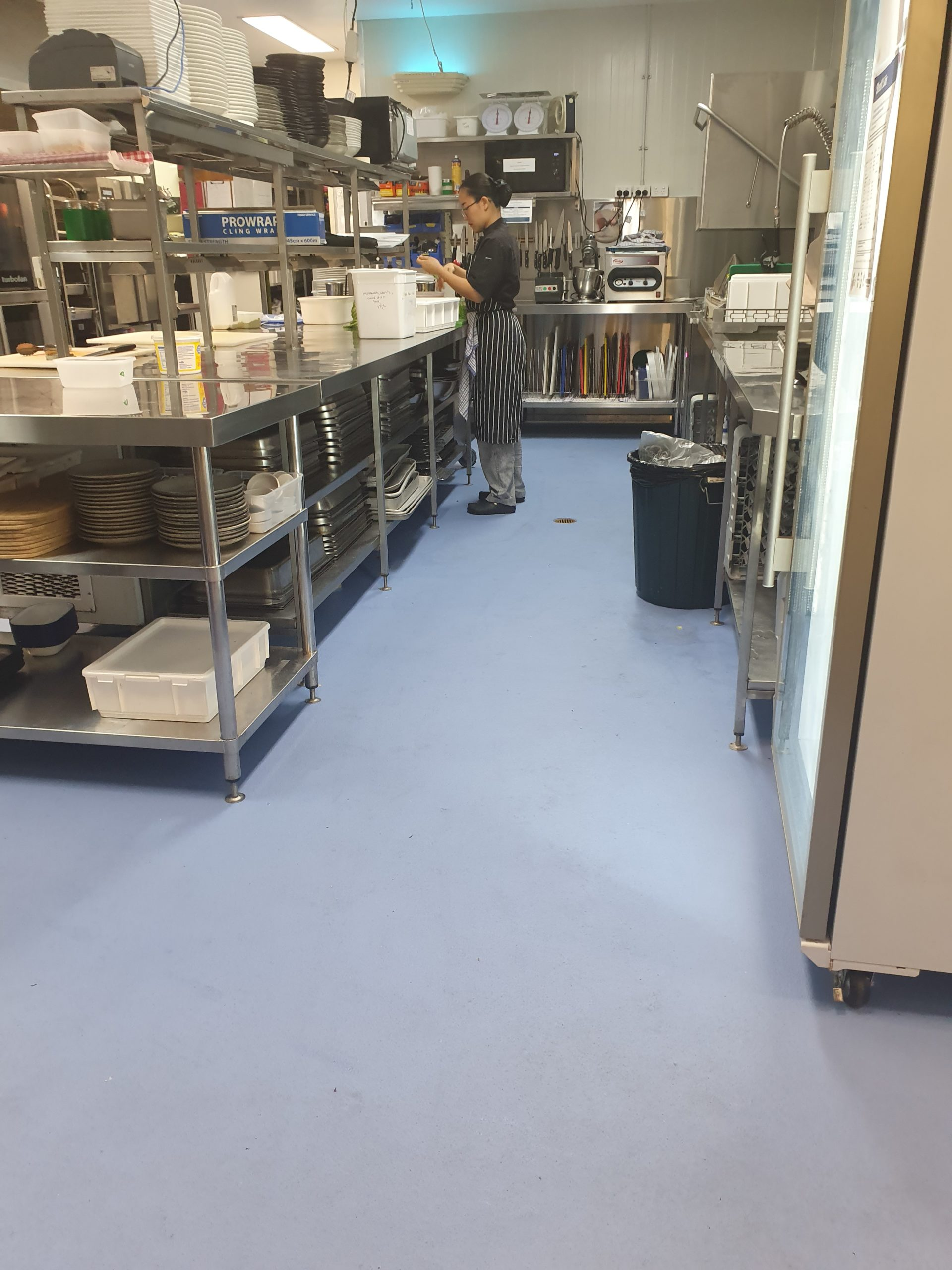 commercial kitchen with a women in the background